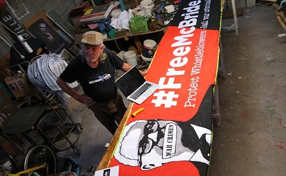 Graeme Dunstan painting the banner to support McBride