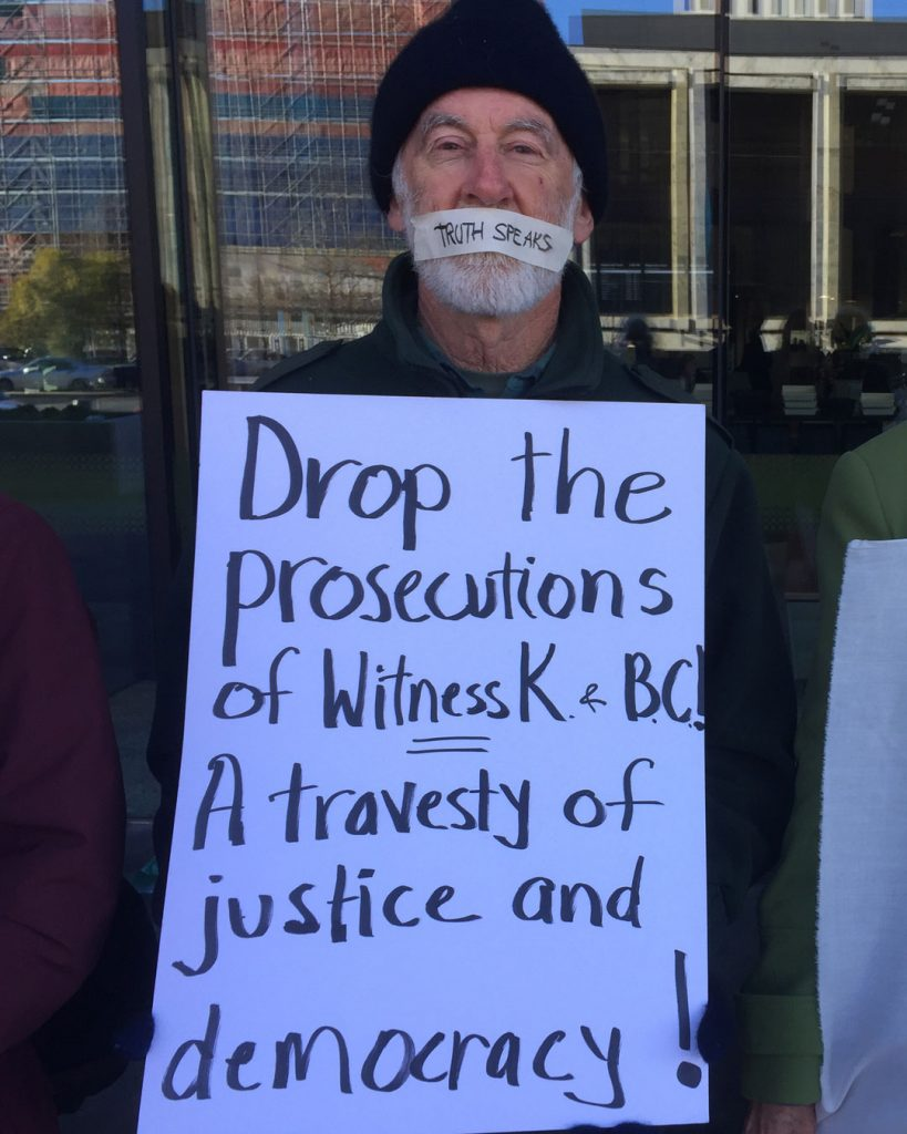 "Person with tape over his mouth saying Truth Speaks, with banner ""Drop the prosecutions of Witness K and Bernard Coleary - A travesty of justice and democracy!"""